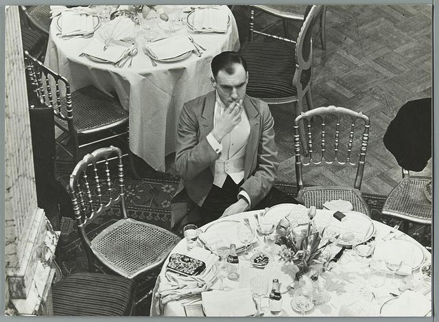 Lonely man smoking in Dutch hotel during a ball. The Netherlands, The Hague, hotel Des Indes, [1936]