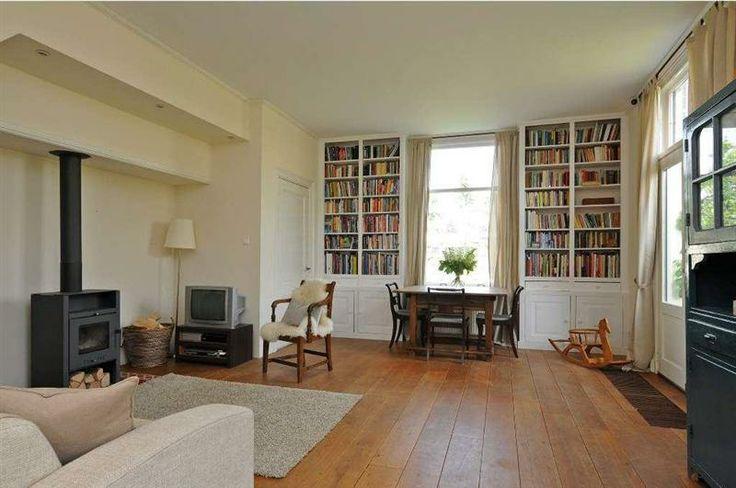 De living vanuit een ander perspectief. De ingebouwde boekenkasten reiken tot aan het plafond en geven genoeg opbergruimte voor kinderspeelgoed en dergelijke. Zuidereinde 31, 's Graveland.