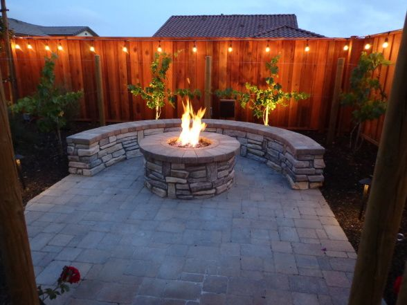 Outdoor Bar, Fire Pit, and Mini Vineyard, This is my husband's dream backyard. It includes an outdoor bar & cooking area, BBQ, fire pit, & mini vineyard. One day we will have patio furniture and chairs by the fire pit, but one thing at a time!, fire pit, built-in stone bench that matches ground pavers, and string lights , Yards Design