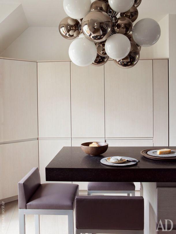 Кухонные фасады сделаны извыбеленного дуба, как истулья, изготовленные назаказ по эскизам Шамсо иобитые кожей. Посуда настоле — изТуниса. Светильник Digit подизайну ЭммануэляБабледа.