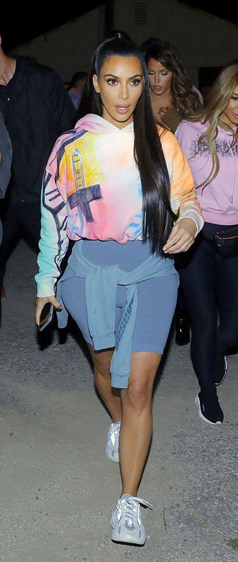 Kim Kardashian wearing grey shorts, sneakers and colorful hoodie. #KimKardashianStyle