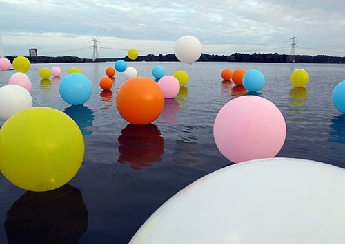 """A whimsical and colourful installation byMerijn HosandRenée Reijnders. The piece features 50 balloons around one metre in diameter that """"shine, float and bubble"""" across the large water expanse Weerwater in Almere, Netherlands. At night, LED lights are inserted into the balloons to create a magical hue-filled glow. I love that no photograph of this installation will ever be the same twice as the balloons dance across the water in a million different ways…"""