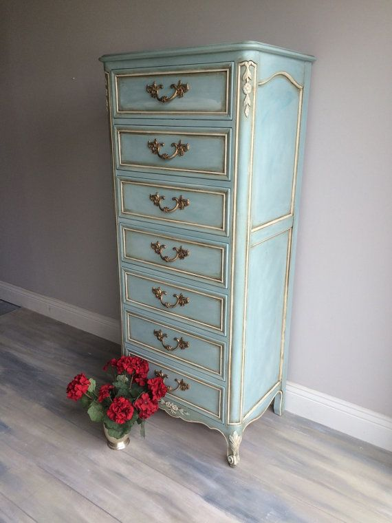 Solid wood, dovetail drawers, french provincial lingerie chest. With maximum storage space, and comforting colors that make the room feel just like home, this one of a kind dresser is essential to stylish storage in your home. Each drawer is finished with sparkling hardware and a subtle but brilliant blue chalk paint, great for any room in need of extra retention. This beauty is layered in paint. It took about 4 different paint shades to achieve this look. Dimensions 57 tall x 23 wide x 16…