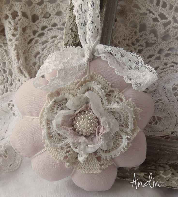 Romantická kytička Shabby chic Dekorační kytička je ušita z jemné látky růžové barvy. zdobení krajkami a štrasovou sponou, Závěs bílá krajka. Lze použít i jako závěsnou dekoraci, do okna, na poličku, na kliky u dveří nebo kličky oken. Průměr 11 cm