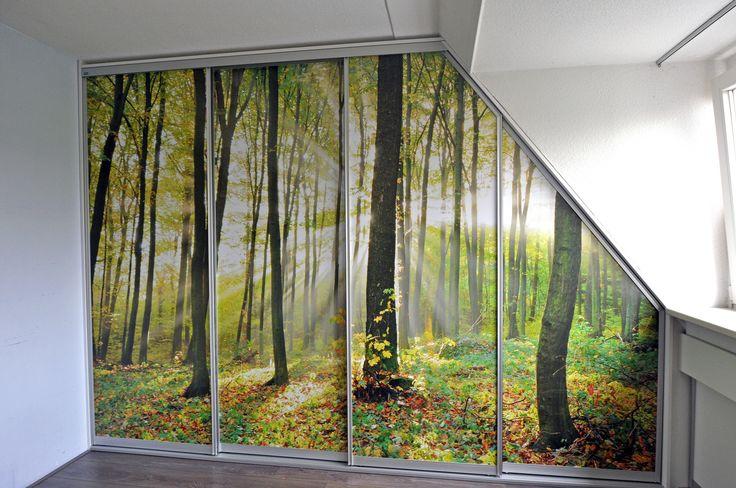mooi schuifdeurkast onder schuin dak met een sticker op de deuren van een bos. gemaakt door klay schuifdeurkasten. www.schuifdeurkastenopmaat.nl