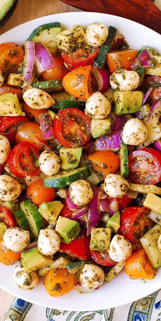 Avocado-Salat mit Tomaten, Mozzarella, Gurke, roten Zwiebeln und Basilikumpü