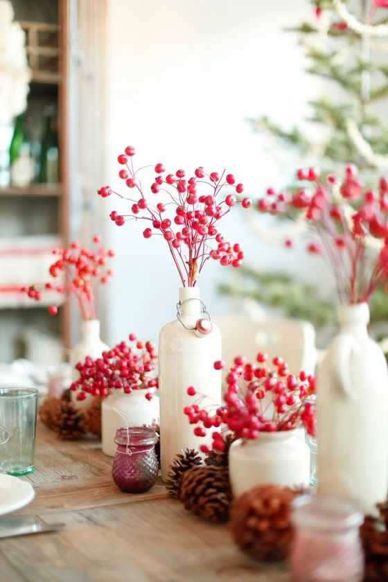 Lovely Christmas table decor with red berries in white bottles.