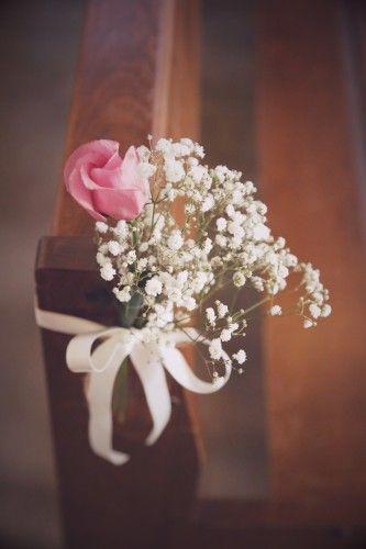 Petite composition florale nouée au banc de l'église par ruban satiné