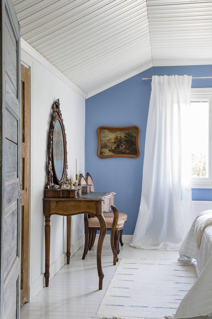 Yläkerran vierashuoneen ikkunaseinä on maalattu Tikkurilan sävyllä H353 Lemmikki. Tuolit ovat Eevan äidin kotitalon peruja. Isän lapsuudenkodista ovat vanha kirjoituspöytä ja sen päälle laitettu piianpeili. Kalustuksen täydentää vanha painokuva, joka roikkui aikanaan Eevan lapsuudenkodin seinällä.