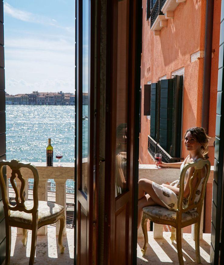 Enjoying a glass of wine on a balcony overlooking a canal in Venice, Italy. Kraska Fox