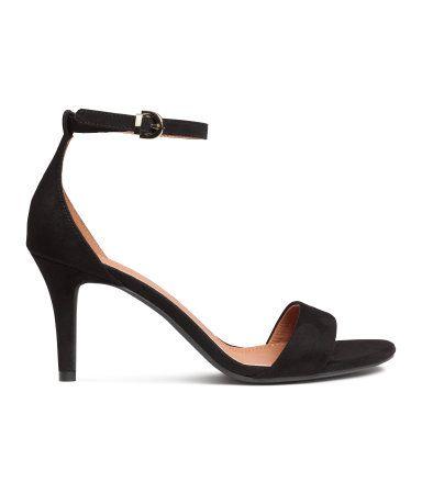 Schwarz. Sandaletten mit bezogenem Absatz und elastischem Knöchelriemen mit Metallschnalle. Futter und Innensohle aus Lederimitat. Absatzhöhe 8 cm. 19,99 €
