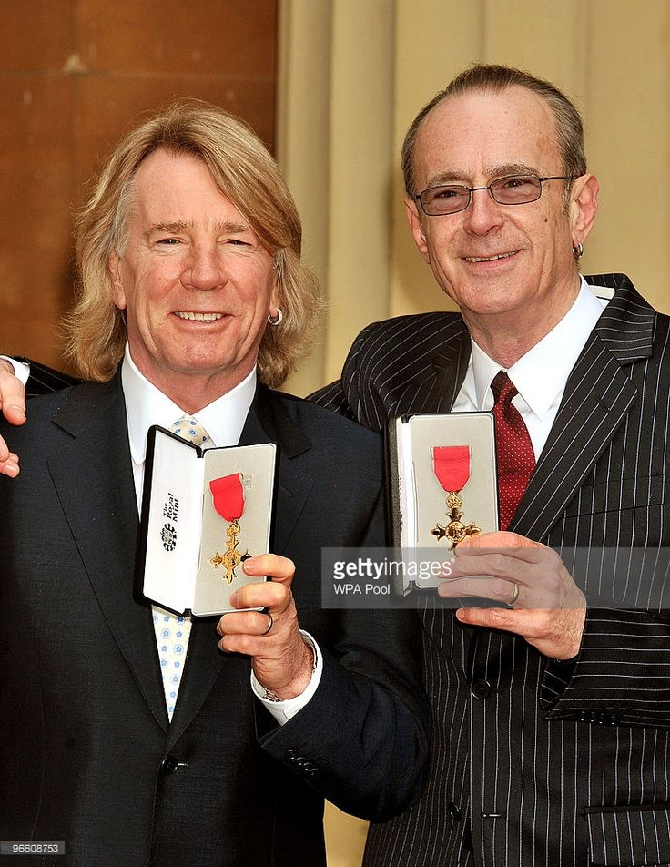 Rick Parfitt and Francis Rossi, founding members of British rock band Status Quo, with the OBE's that were awarded to them by Britain's Queen Elizabeth II during an investiture ceremony at Buckingham Palace on February 12, 2010 in London, England.