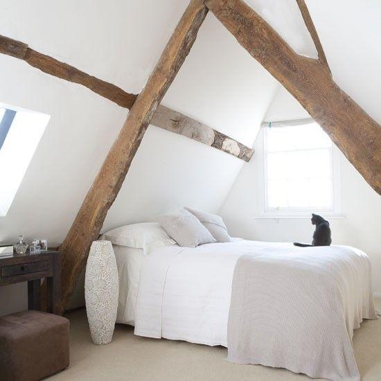 Schlafzimmer im Dachgeschoss mit Balken Lassen originalen Balken zum Brennpunkt aus einem Schlafzimmer, indem sie ein System weiß werden. Dick gestrickte Decken und Kissen aus weichem, grauen hinzufügen Wärme.