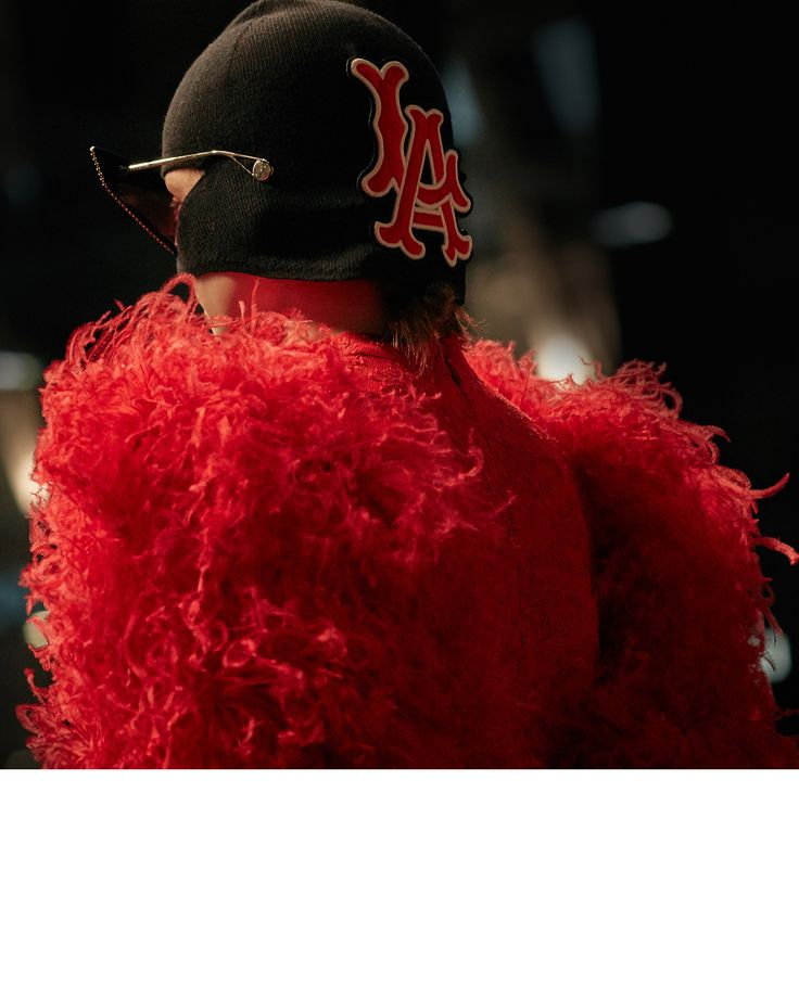 Feathered sleeves and the @paramountpics logo features on a long organza and lace dress gown worn with a hat featuring the initials of Major League Baseball team Los Angeles @angels in the #GucciFW18 fashion show. #AlessandroMichele #mfw   TM, ® & ©2018 Paramount Pictures.  All Rights Reserved   Major League Baseball trademarks and copyrights are used with permission of Major League Baseball Properties, Inc.
