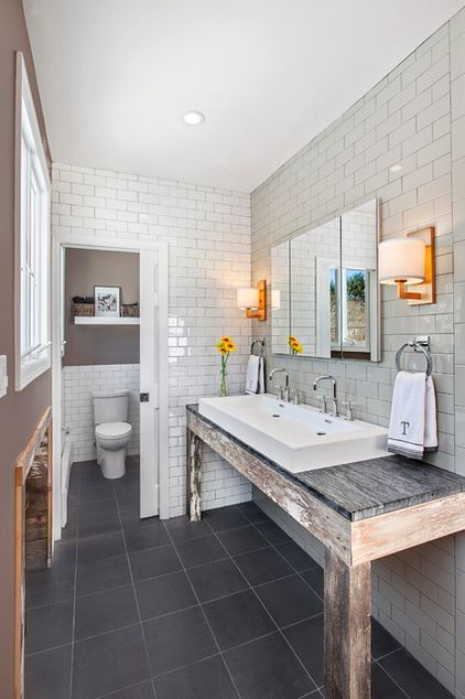 Combine reclaimed wood with soapstone countertops. The combination of the sanded-down white paint on the reclaimed-wood base and the veins in the countertop tie the two pieces of this vanity together in a unique way. A long trough sink and a frameless mirror create a clean look.