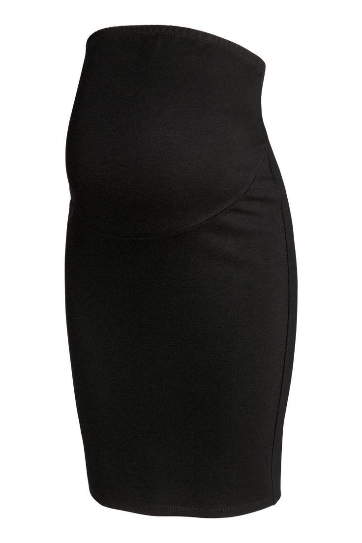 Svart. En stretchig kjol i trikå. Ofodrad. Bred mudd upptill för bästa passform över magen.