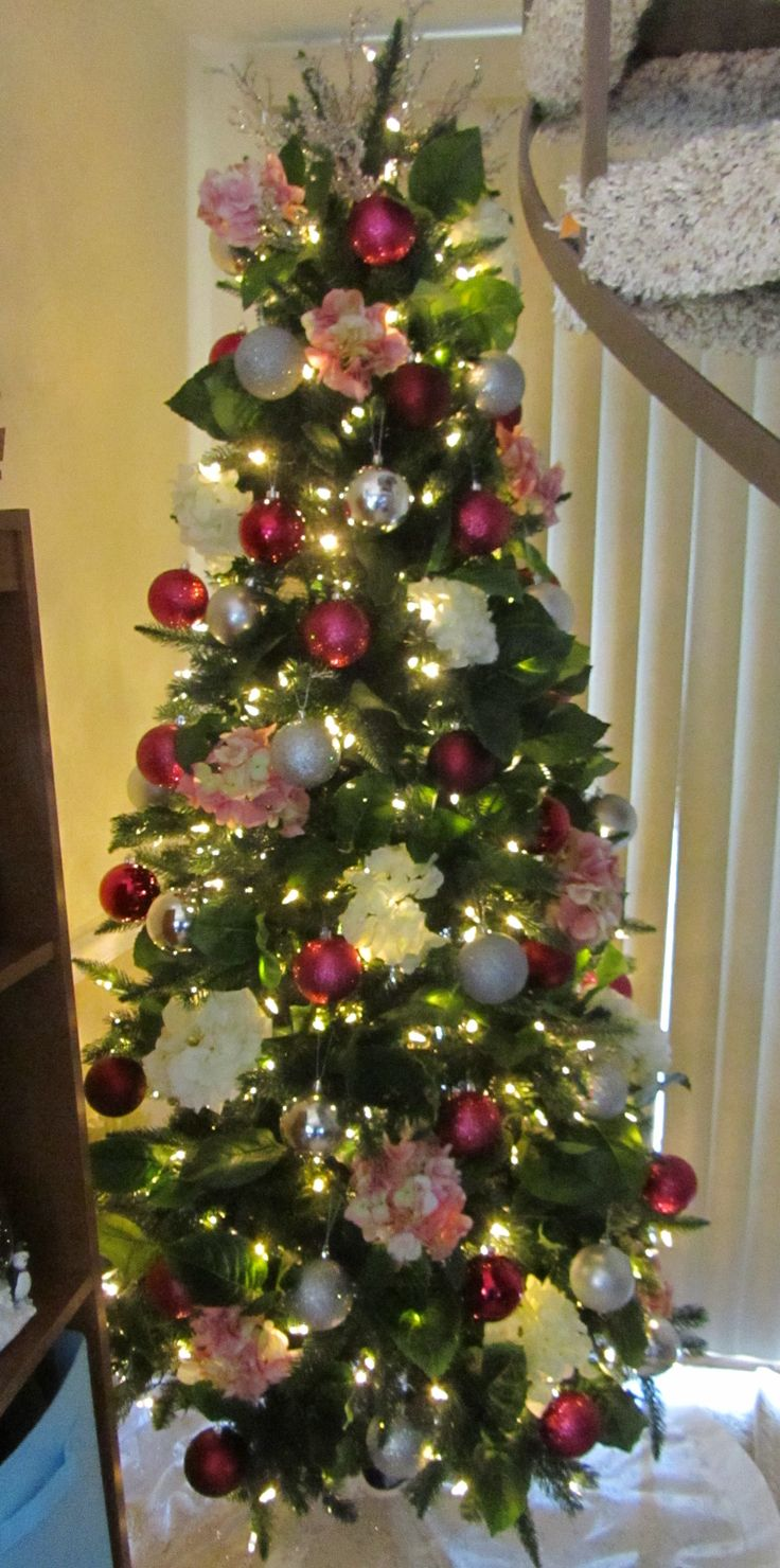 Our tree 2016 - Raspberry & Silver ornament balls, pink & white hydrangea's, hydrangea leaves throughout the tree and iced branches at the top.