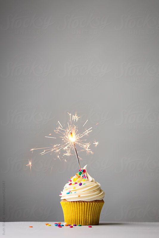 Cupcake with sparkler on grey by RuthBlack | Stocksy United
