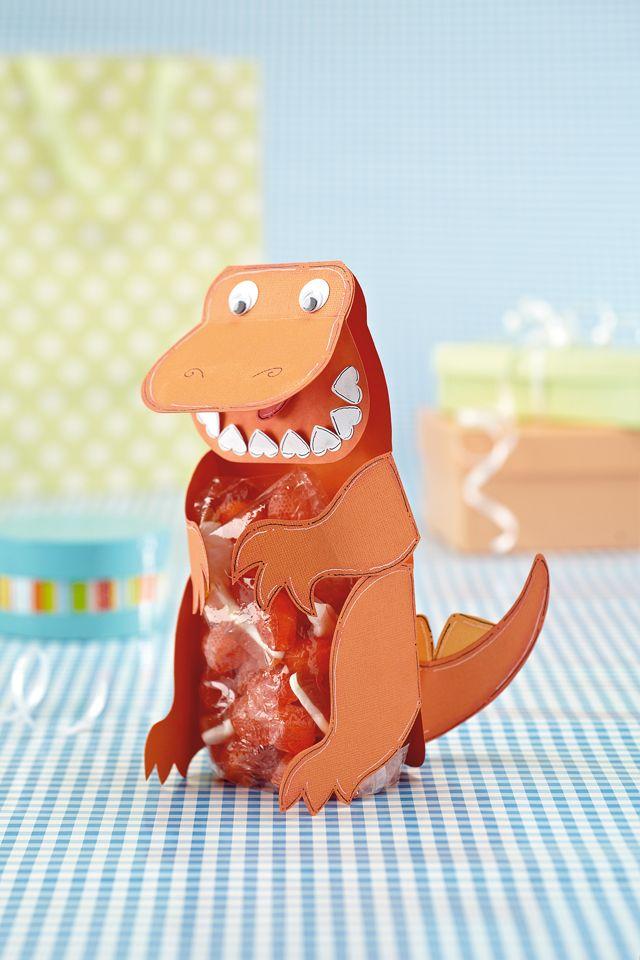 """Dinosaur gift bag. Nodig: Bijlage, Karton wit/rood/2 groen, Potlood, Oogjes, Traktatie, Foliezakjes, Dubbelzijdig tape. Werkwijze: Print bijlage & knip onderdelen uit. Trek hartjes over op wit & gr. karton. Trek dino + 1 kop extra over op d. gr. karton Teken tong op ro. karton. Knip onderdelen uit. Vouw kop & poten, Plak losse kop met rand achter gevouwen kop. Plak de tandjes & tong in mond. Plak de wiebeloogjes op & gekl. """"tandjes"""" op staart. Vul zakje met traktatie & plak op buikje v.d…"""