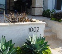 This beautiful small home entry combines plaster with travertine paving and wall caps