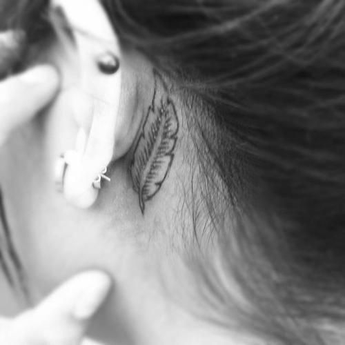 Pretty behind the ear feather tattoo.