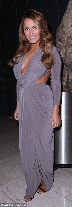 Gorgeous: The former TOWIE star looked typically glamorous in a plunging dove grey gown which featured provocative cut-out detailing around her torso, which looked as slim as ever