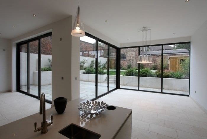 Staggered glass structure bi fold doors onto patio area for Sliding glass doors onto deck
