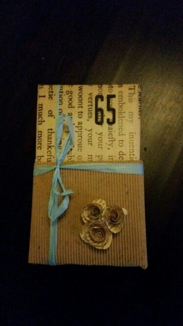 Gift wrapping for an e-reader with paper flowers from old bookpages