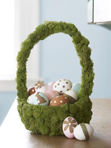 Showcase twine-wrapped and paper-embellished eggs with this woodsy, moss-covered creation. Simply hot-glue craft-store moss to an inexpensive basket; for the eggs, use a glue stick to add petals, polka dots, bunnies, and string. #Easter