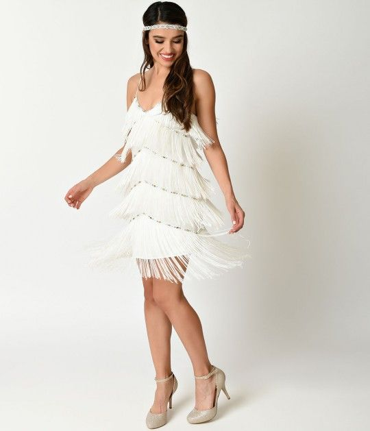 Fringe forever, darlings. A lightweight and airy flapper dress complete in a stunning off white, cast in a modern semi-fitted silhouette. Beautifully bordered with gold and silver crystal beading, generous tiered fringe covers this entire dress. Supported