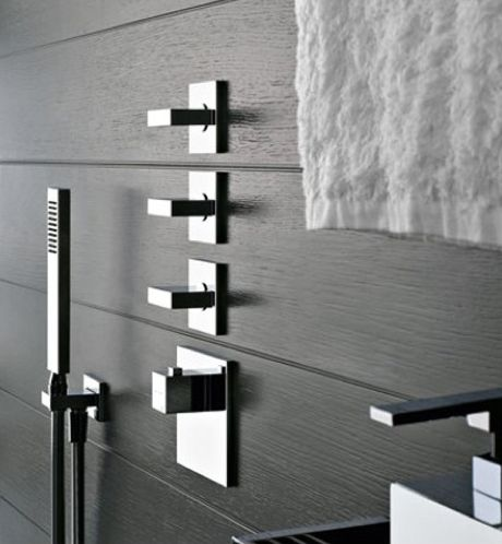 Gessi Rettangolo bathroom fixtures on a wood walled shower.