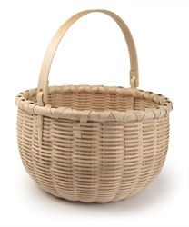 """Bushwhacker Basket  10.5"""" dia. x 12"""" h  Tony Stubblefield    This is technically not a Shaker basket, but a Bushwhacker style basket. The Bushwhackers were basketmakers from New York state and their baskets were often confused with those made by the Shakers. Bushwhacker baskets often featured a swing handle and a """"bump bottom"""". This version is made of materials I processed myself, including brown ash weavers/uprights, white ash ears and maple handle and rims."""