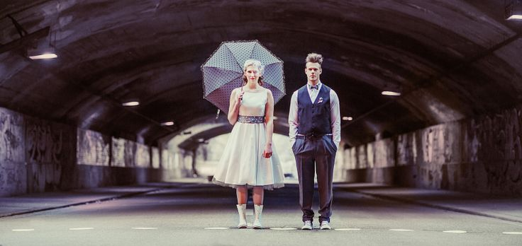 Brautpaar im 50er Jahre rockabilly Look, Petticoat Brautkleid mit grauem Tüllrock, Regenschirm in grau mit weißen Punkten und passenden Acce...