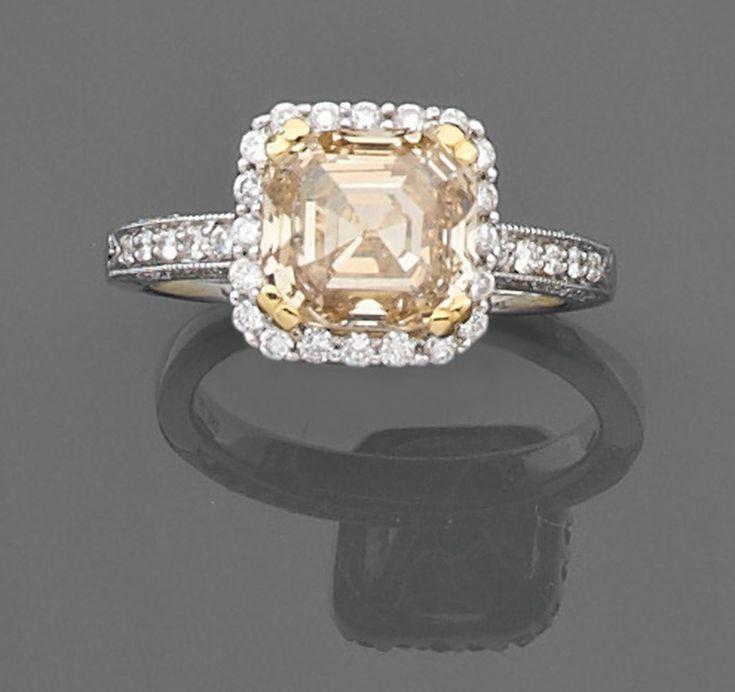Bague  en or gris ornée d'un diamant de forme carrée à degrés et à pans coupés couleur champagne entouré de petits diamants blancs. Anneau partiellement serti de petits diamants blancs.  Poids brut : 5 gr.  Poids du diamant : 3,13 carats    A 3,13 carats diamond and gold ring.