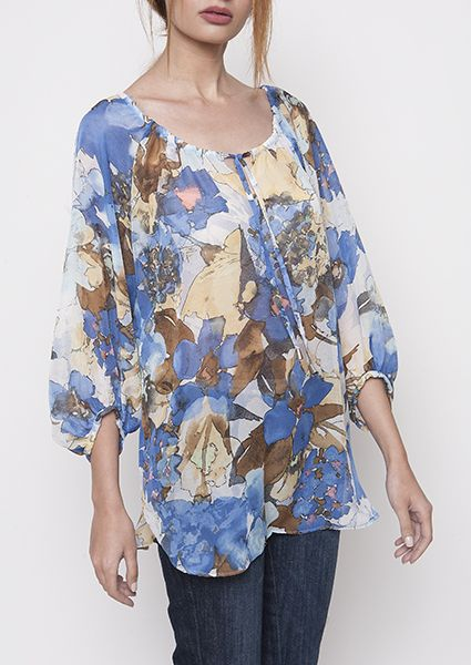 Blouse in beautiful printed  fabric rwhich remindes a watercolor table with a comfortable neckline and wide sleeves ended with pleat