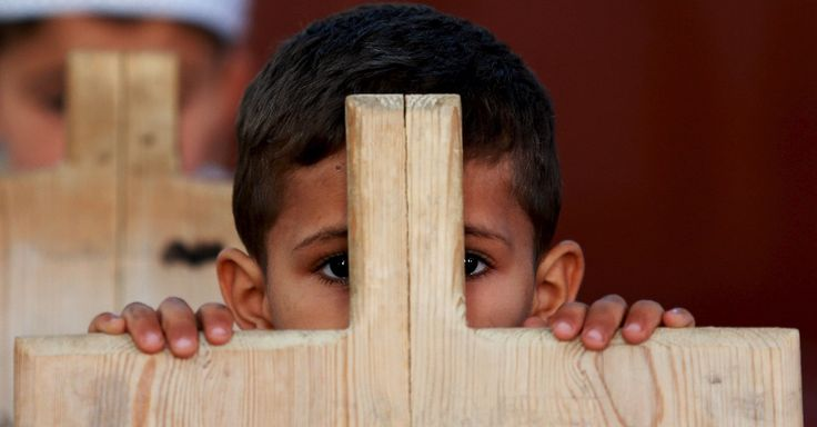 Garoto recita versos do Alcorão, escritos em tábua de madeira, durante o período escolar na cidade de Benghazi, na Líbia