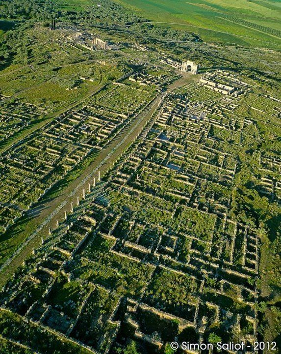 Volubilis, Morocco. Volubilis is a partly excavated Roman city in Morocco situated near Meknes between Fes and Rabat. Built in a fertile agricultural area, it was developed from the 3rd century BCE onwards as a Phoenician settlement, and later, Roman.