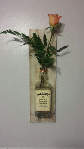 Jack Daniels hanging vase. I got lucky and had all the supplies to make this already at home. I made a second one as well and hung them parallel on either sides of a framed sailor jerry poster.  -Found wood -alcohol bottle  -rose -claw tooth bracket -copper sheeting cut into a strip and nailed to the wood Around the top of the bottle