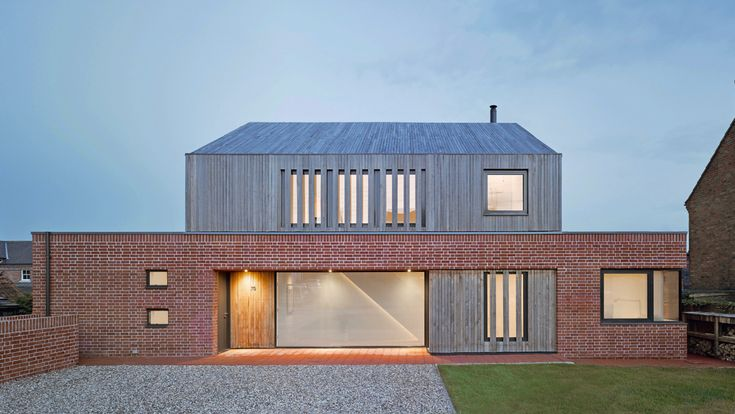 Front view of the house at Broad Street in Suffolk by Nash Baker Architects, showing the local handmade red bricks used on the ground floor, and the oak cladding wrapping around the first floor.
