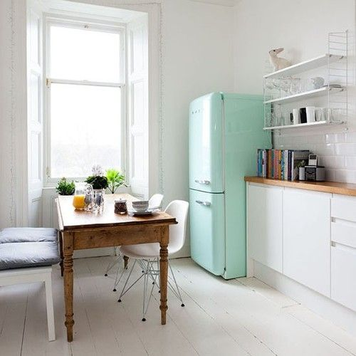 Super little apartment kitchen. White paint, natural wooden table and feature mint green SMEG fridge freezer. The window sells it….lots of natural light. If you're decorating to sell…keep it simple! Please!