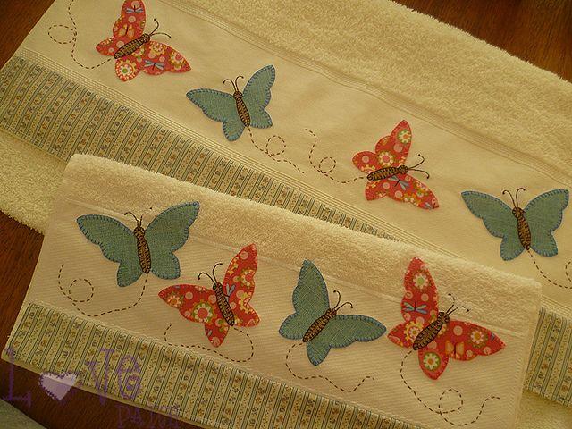 Tolha de banho com aplicação de borboletas.