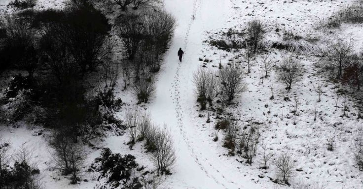 Um homem caminha nesta em um parque de Derry, na Irlanda do Norte, coberto de neve.  Fotografia: Cathal McNaughton/ Reuters.