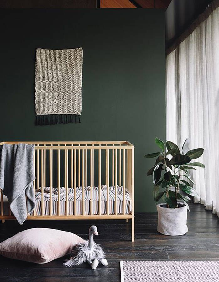 Very minimalistic nursery with a dark green wall