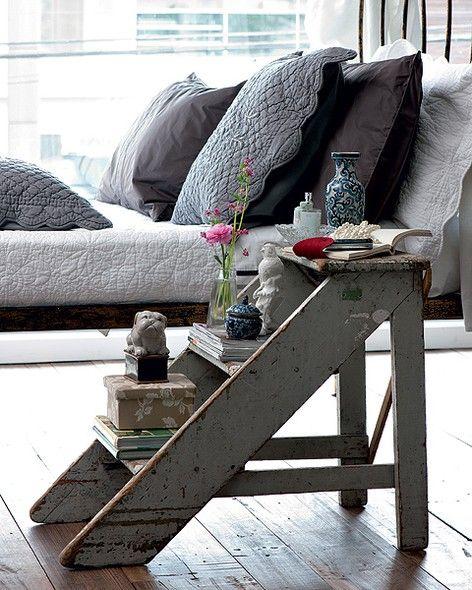 Transformada em criado-mudo, a escada pintada de cinza com aparência desgastada deixou este quarto com ar romântico