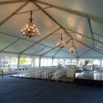 Large tent with chandeliers, staging, and white chairs for wedding