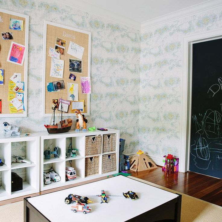Boy's playroom features walls clad in vintage world map wallpaper lined with an…