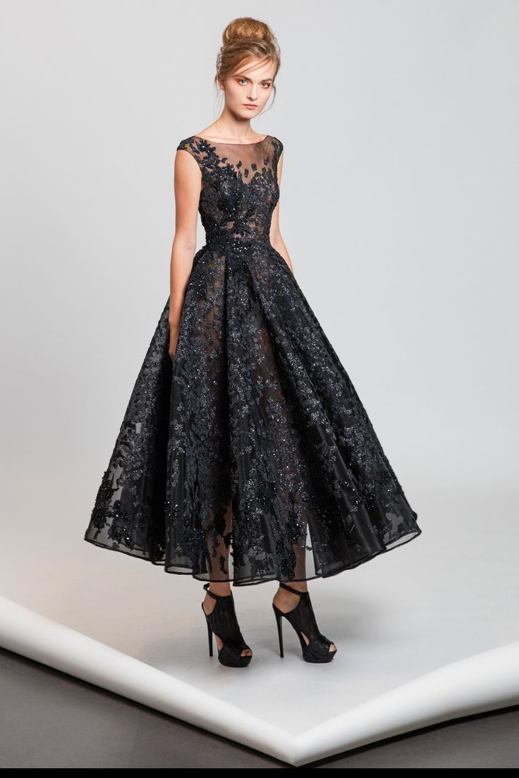 Tea-length A-line black dress with sheer neckline in embroidered tulle featuring sequins and flowery appliques.