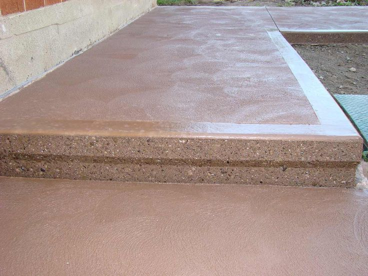 Beautiful terra cotta coloured textured concrete with exposed aggregate step creates a unique look for this sidewalk.
