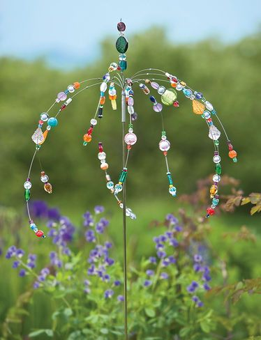 I know I can make this!!!!! DANCING GARDEN JEWELS STAKE.. It's hard not to smile when you see these sparkling Dancing Garden Jewels bobbing and swaying in the breeze. The multicolored glass beads are strung on flexible, stainless steel wires. this looks really easy to make. glass beads and craft wire attached to rebar or something similar