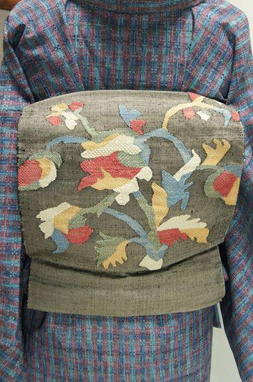 ベージュとブラックの糸が織り交ぜられた素朴な風合いのあるグレーの地に、ボヘミアンファブリックを思わせる装飾模様が織り出された紬のつくり帯です。